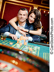Woman embracing gambler at the roulette table