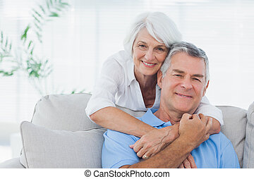 Woman embracing husband sitting on the couch