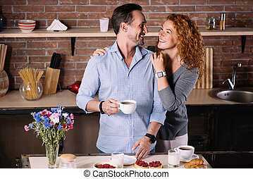 Woman embracing man in the kitchen