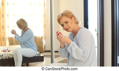 Woman embroider a picture, but she has poor eyesight and she...