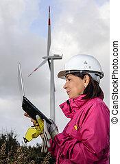 Woman engineer checking wind turbines. - Engineer woman...
