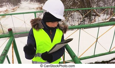 Woman engineer inspecting sluices in cold winter day
