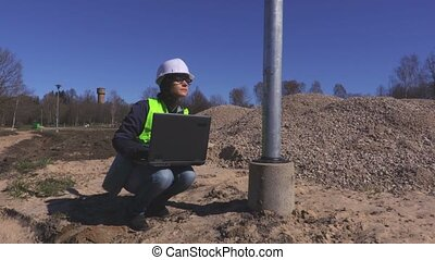 Woman engineer is using laptop at construction site