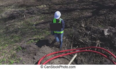 Woman engineer near cables in plastic pipes