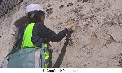 Woman engineer near old damaged wall