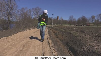 Woman engineer on the road near ditch