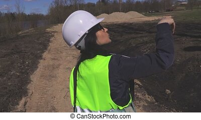 Woman engineer walking and talks about construction site