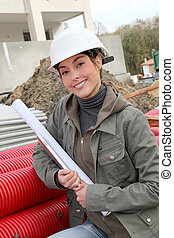 Woman engineer with white security helmet standing on construction site