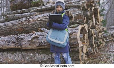 Woman engineer writing near pile of logs in snowfall