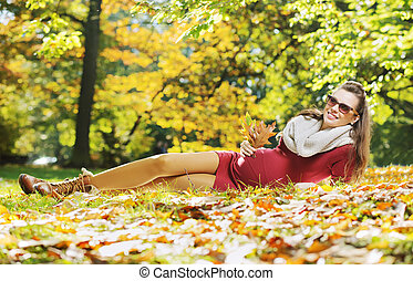 Woman enjouing the golden autumn - Pregnant woman enjouing...