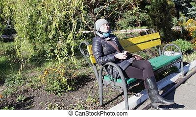 woman enjoy sunlight on a bench in autumn