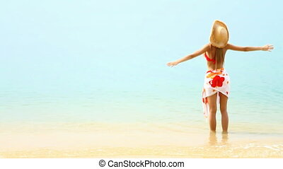 Woman enjoy warm tropical water at sandy exotic beach