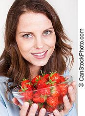 Woman enjoying a bowl of strawberries