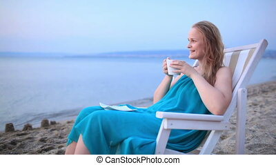 Woman enjoying a cup of tea at the seaside