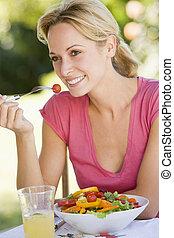 Woman Enjoying A Salad In A Garden
