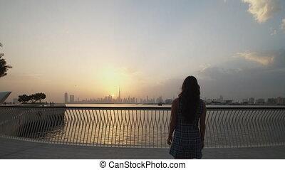 Woman enjoying a sunset in Dubai. Stunning Dubai cityscape with skyscrapers during beautiful golden hour warm light 4K