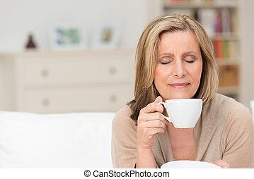 Woman enjoying an aromatic cup of coffee