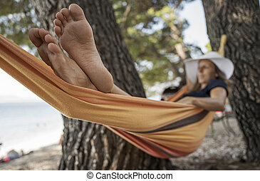 Woman enjoying and resting in range hammock looking at the sea