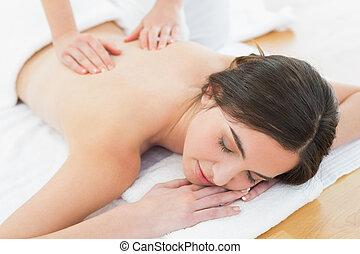 Woman enjoying back massage at beauty spa - Close up of a...