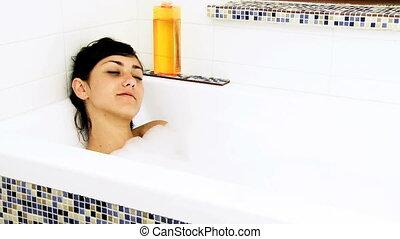 Woman enjoying bath with foam