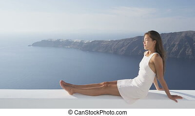 Relaxed young woman enjoying beautiful view of caldera and sea on Santorini, Greece. Luxury lifestyle woman in white sundress is relaxing during summer vacation. RED PIC 96 FPS.