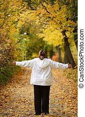 Woman enjoying beauty of Autumn