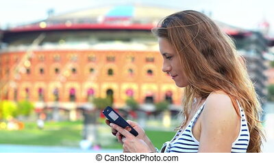 Beautiful woman using a smartphone, city lights in the background