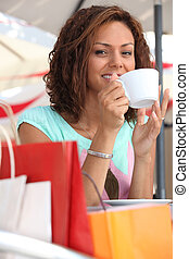 Woman enjoying coffee during shopping trip