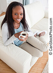 Woman enjoying coffee on couch