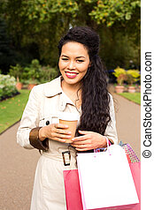 woman enjoying coffee with shopping bags.
