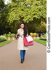 woman enjoying coffee with shopping bags