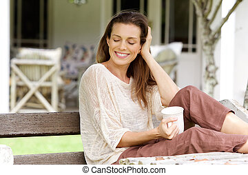 Woman enjoying cup of coffee at home garden