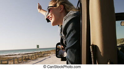 Woman enjoying free time during road trip - Side view of a ...