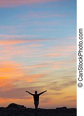 Woman enjoying freedom at sunset.