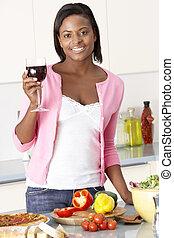 Woman Enjoying Glass Of Wine In Kitchen