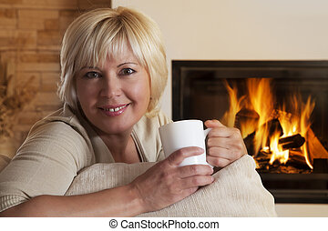 Woman enjoying hot drink by home fireplace - Adult woman ...