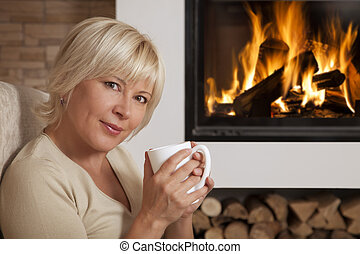 Woman enjoying hot drink near home fireplace - Adult woman ...