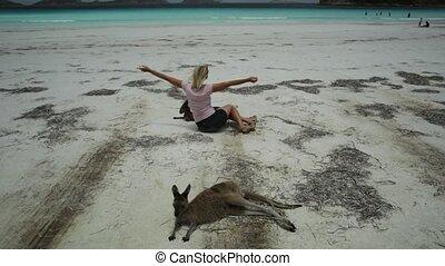 Woman enjoying kangaroo at Lucky Bay - Happy caucasian woman...