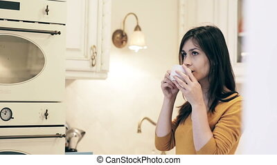 Woman enjoying morning coffee on a bright kitchen -...