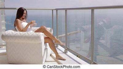 Woman enjoying morning on hotel balcony - Content young girl...