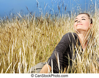 Woman enjoying on the wheat field