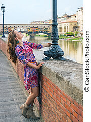 Woman enjoying promenade along embankment near Ponte Vecchio...