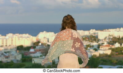 """Woman enjoying sea breeze on hill, looking at seaside town. Feeling of freedom"""