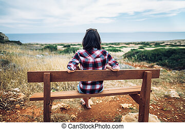 Woman enjoying sea view sitting on a bench in beautiful valley