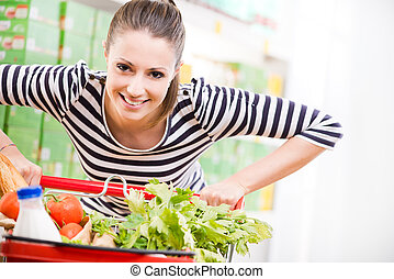 Woman enjoying shopping at supermarket - Attractive young...