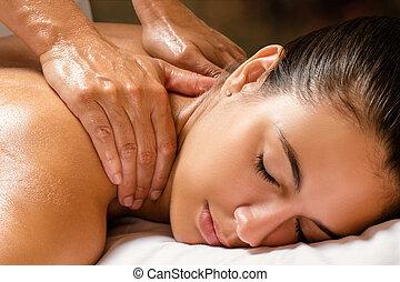 Woman enjoying shoulder massage in spa.