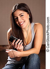 Beautiful young smiling woman using smart phone to listen to music while relaxing at home. Girl is dressed very casual in a grey vest and blue jeans, looking straight into the camera.