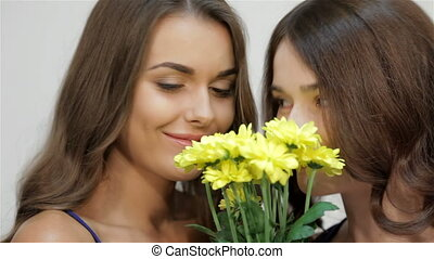 Woman enjoying smelling yellow aromatic flowers isolated on white background. Girls sniffing flowers. Beautiful woman with flowers