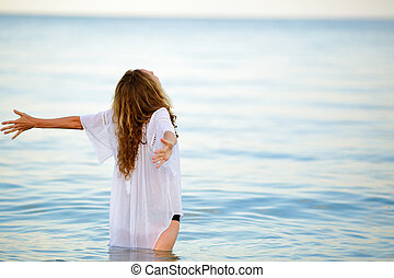 Woman enjoying summer freedom with open arms at the beach