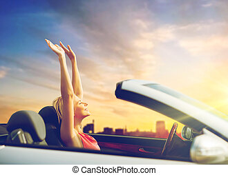 woman enjoying sunset in convertible car over city